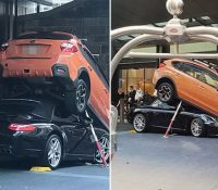 Un aparcacoches aparca un Porsche 911 debajo de un Subaru