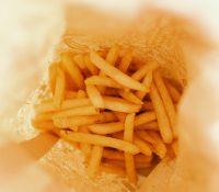 Una joven demuestra tener la boca más grande del mundo con una caja grande de patatas fritas